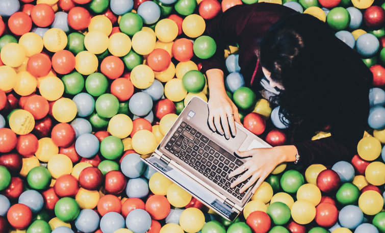 Women working with computer in a ball pit