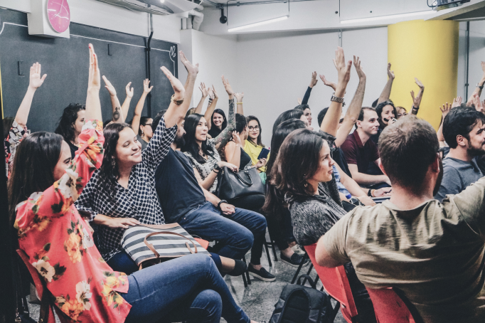 Young entrepreneurs raising hands in an event